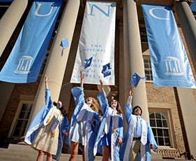 UNC grads in blue gowns tossing caps