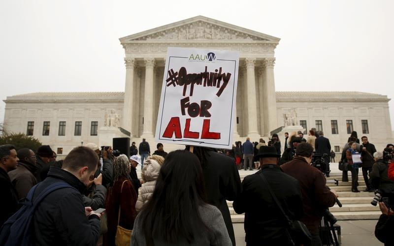 A demonstrator holds a sign aloft as the affirmative action in university admissions case was being heard at the Supreme Court in Washington, December 9, 2015. REUTERS/Kevin Lamarque