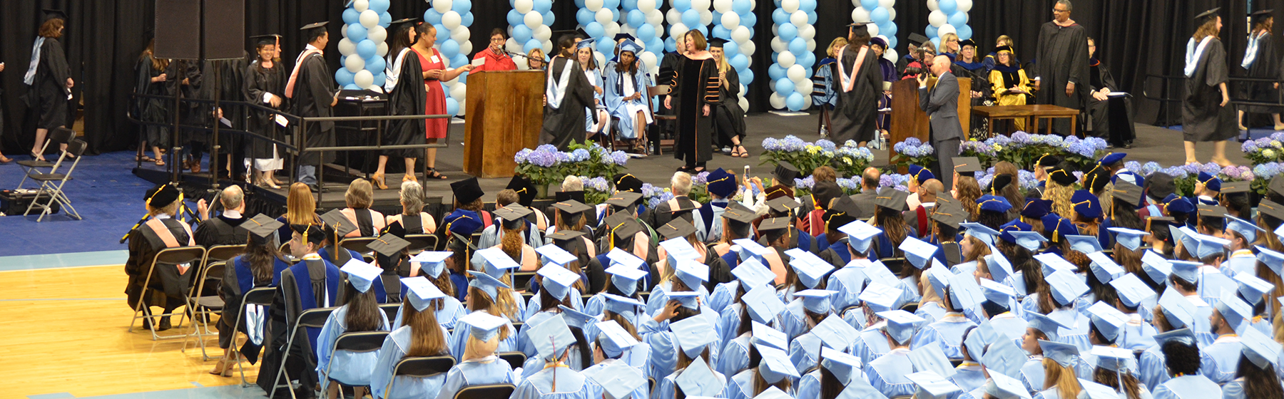 Students walk across the stage at the 2019 Gillings School Spring Commencement.