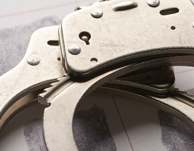 Pictured are handcuffs on top of a fingerprint chart.