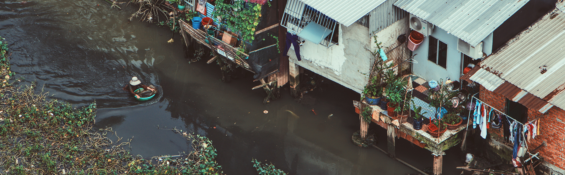 A person swims in a river that is flanked by houses with tin roofs.
