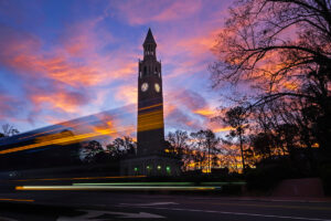 The UNC-Chapel Hill bell tower stands against a colorful sky at sunrise.