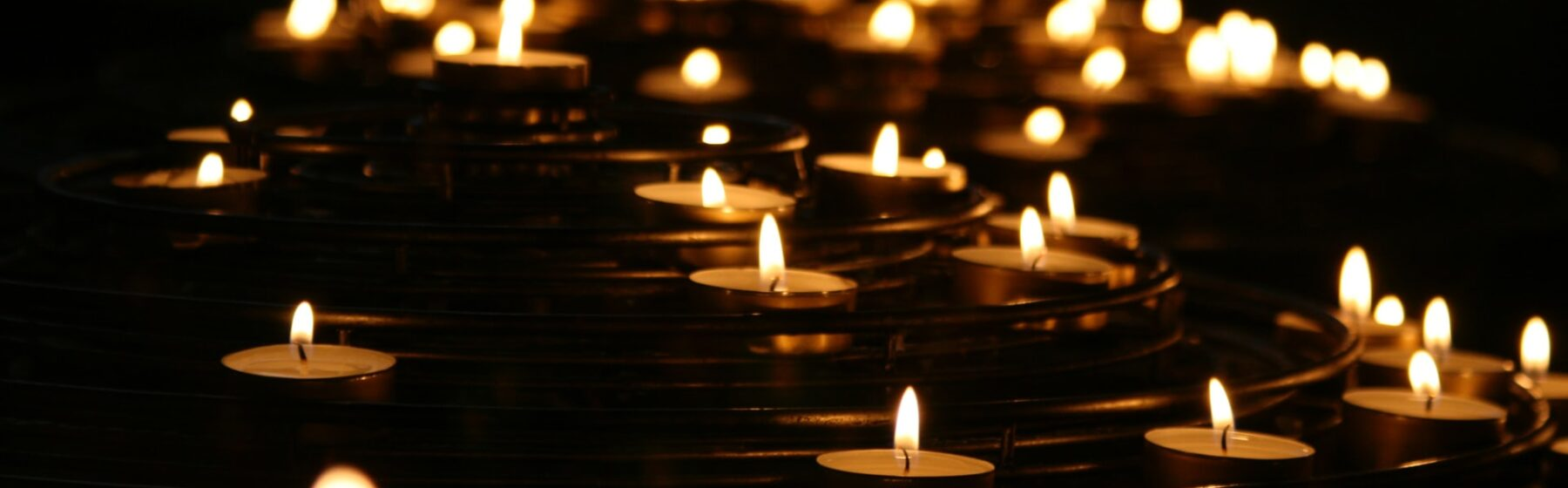 A multitude of candle flames shine against a dark background.